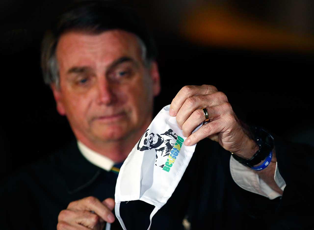 O presidente Jair Bolsonaro com máscara com sua imagem estampada