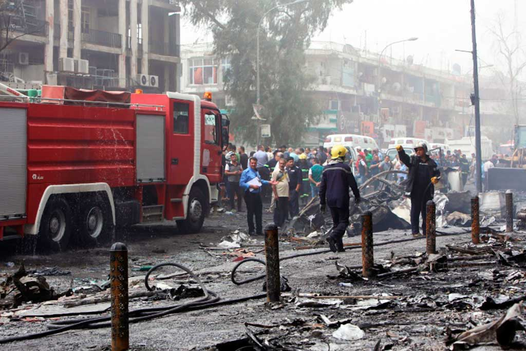 Iraquianos, incluindo bombeiros, no local de um atentado suicida reivindicado pelo grupo Estado Islâmico, no bairro de Karrada, Bagdá