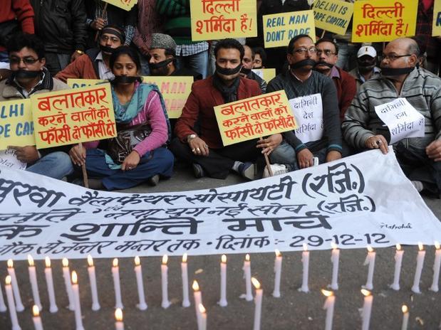 Amordaçados em frente a velas acesas, manifestantes prestam homenagem à vítima de estupro na Índia